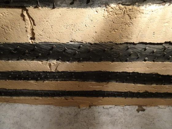 Plafond ancien « isolé ». L'intervalle entre le poutres est garni de mortier. Les poutres sont hérissées de clous pour faire accrocher le plâtre qui enduisait l'ensemble du plafond (ferme Elzéard La Combe).